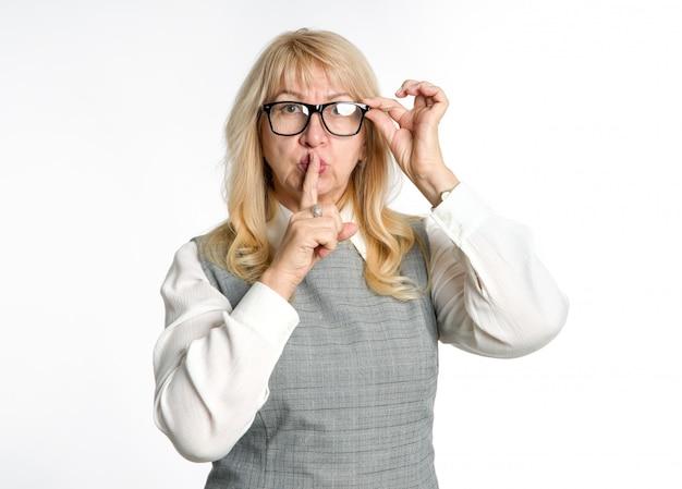 Silenzioso! la donna in piedi in bicchieri mostra un gesto di silenzio su uno sfondo chiaro. tieni il dito vicino alle labbra.