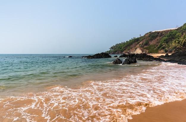 Onde tranquille sulla spiaggia di vagator vasco da gamma. goa india.