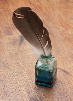 Penna d'oca in un calamaio di vetro su un tavolo di legno