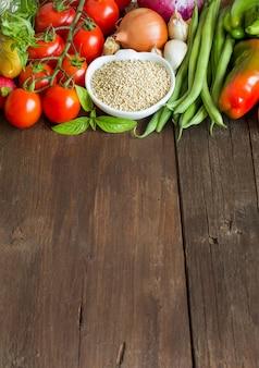 Quinoa in una ciotola e verdure fresche si chiudono su un tavolo in legno con copia spazio