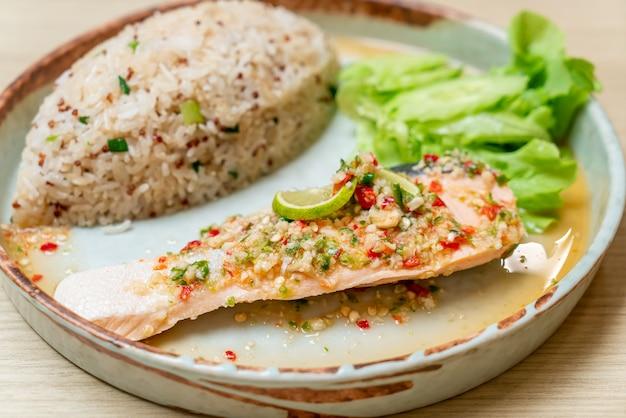 Riso fritto alla quinoa con salmone al vapore condito con peperoncino e lime. stile di cibo sano