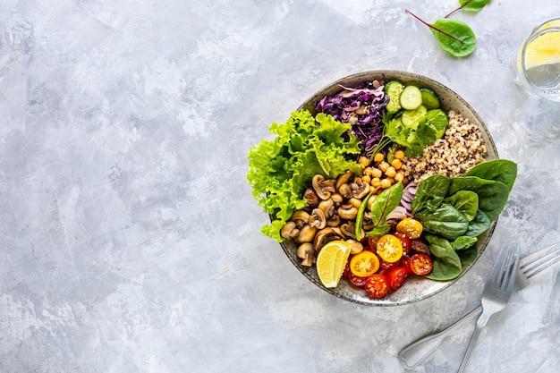 Quinoa, funghi, lattuga, cavolo rosso, spinaci, cetrioli, pomodori, una ciotola di buddha su bianco, vista dall'alto.