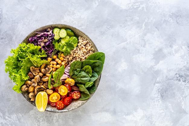 Quinoa, funghi, lattuga, cavolo rosso, spinaci, cetrioli, pomodori in una ciotola di buddha