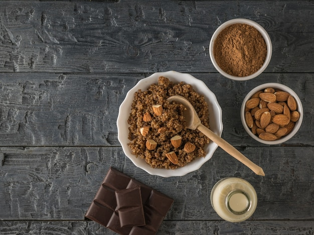 Porridge di quinoa con mandorle e latte su un tavolo di legno. dieta sana. disposizione piatta.