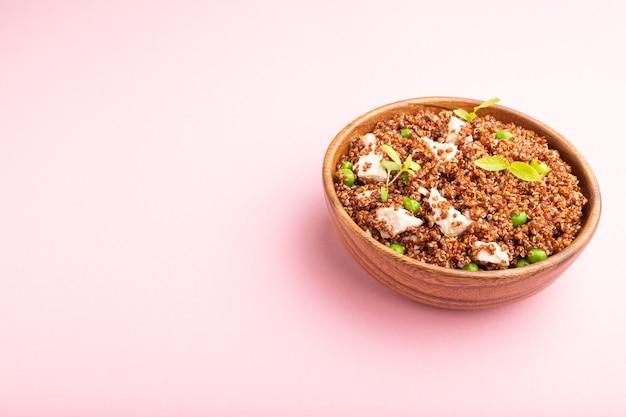 Porridge di quinoa con piselli verdi e pollo in una ciotola di legno su una superficie rosa pastello