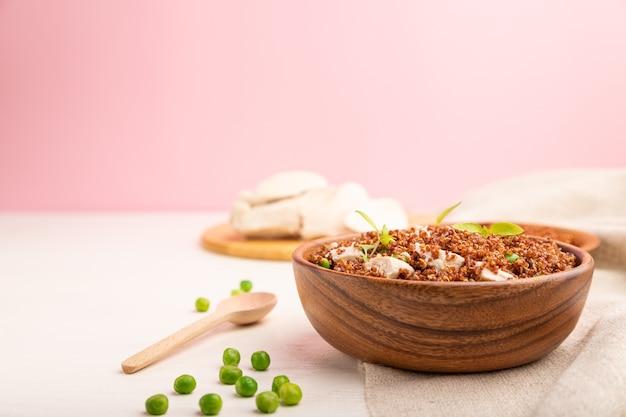 Porridge di quinoa con piselli verdi e pollo in una ciotola di legno. vista laterale, copia dello spazio.
