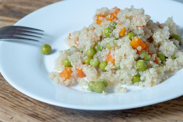 Porridge di quinoa con verdure e avocado in un piatto piatto bianco su una tavola di legno. concetto di supercibi e vista dall'alto.