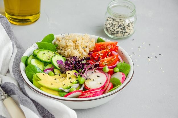 Insalata di quinoa con verdure fresche, spinaci, piselli, microgreens e semi di sesamo in una ciotola