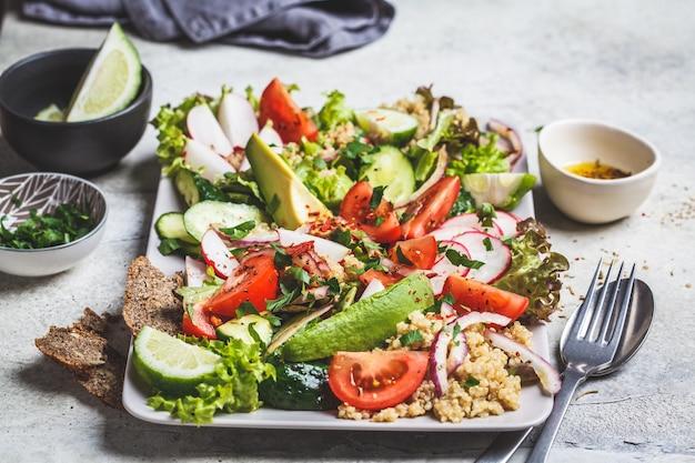 Insalata di quinoa con pomodoro, cetriolo, ravanello e avocado su un piatto rettangolare grigio. concetto di cibo vegano sano.