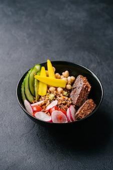 Quinoa con succosa cotoletta vegana, cetriolo, ravanello, mini mais e ceci su sfondo scuro