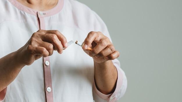 Smetti di fumare, giorno senza tabacco, le mani della mamma rompono la sigaretta