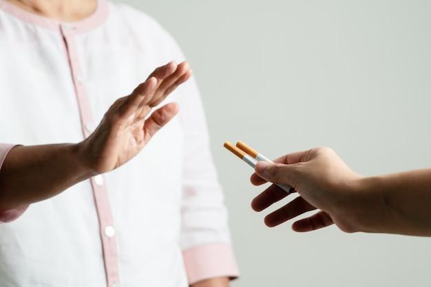 Smettere di fumare, giorno senza tabacco, gesto delle mani della madre rifiutare la proposta di sigaretta, messa a fuoco selettiva