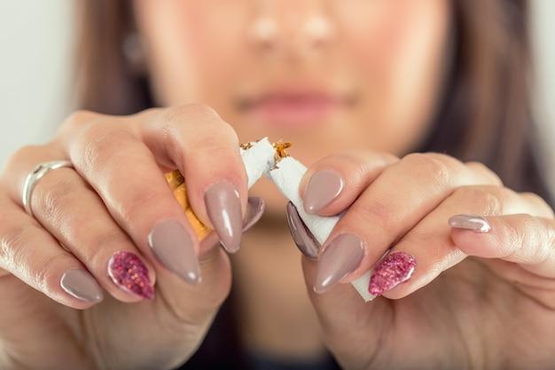 Smettere di fumare. mani di donna che rompono il mazzo di sigarette.