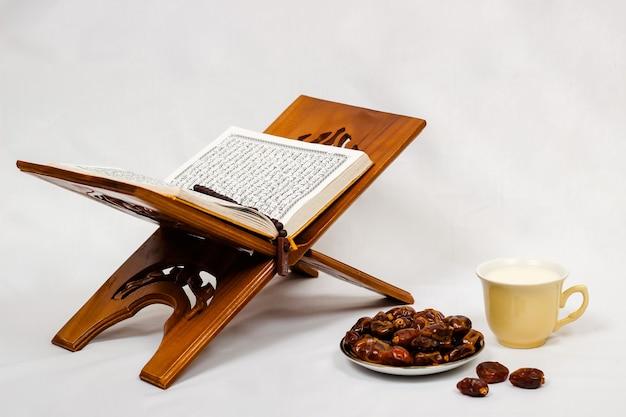 Date del corano e un bicchiere di latte isolato su uno sfondo bianco