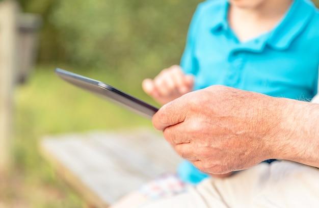 Ãâƒã'â¢ãƒâ'ã'â ãƒâ'ã'â®primo piano delle mani del nonno utilizzando una tavoletta elettronica con suo nipote su una panchina. concetto di valori di generazione