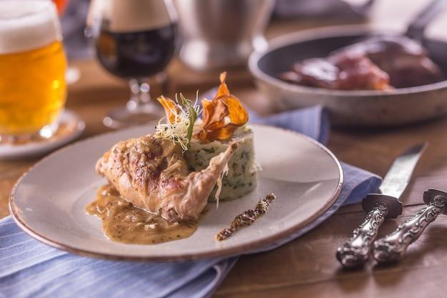 Coscia di coniglio con purè di patate e decorazione su piatto in ristorante.