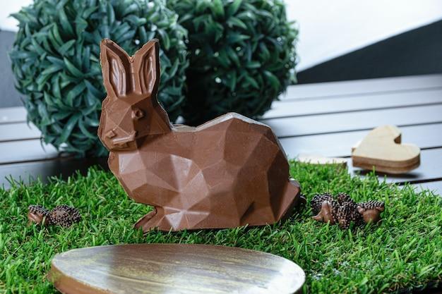 Cioccolato a forma di coniglio su un prato finto. in primo piano, uovo di pasqua al cioccolato.