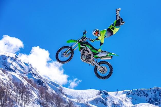 Corridore su una moto in volo, salta e decolla su un trampolino contro le montagne innevate
