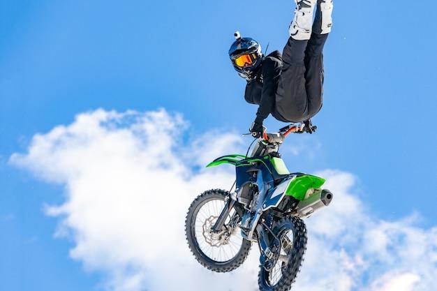 Corridore su una moto in volo, salta e decolla su un trampolino di lancio contro le montagne innevate