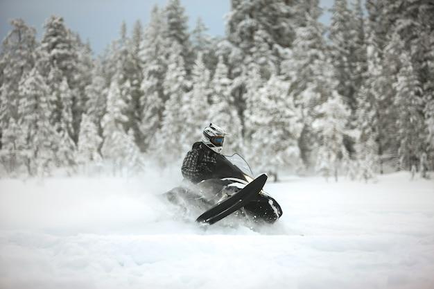 Il corridore in sella a una motoslitta e alla deriva su una superficie innevata all'aperto nella natura