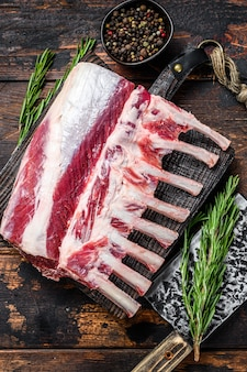 Carré di carne cruda di agnello con osso su un tagliere. fondo in legno scuro. vista dall'alto.