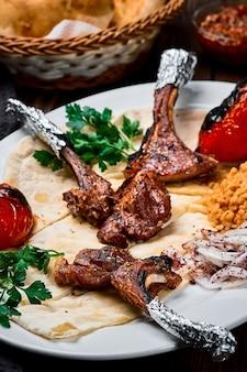 Carré di agnello o pirzola kuzu turco con bulgur, verdure grigliate e spezie su un piatto bianco. sfondo di legno scuro, da vicino