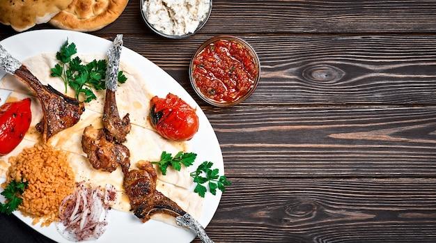 Carré di agnello o pirzola kuzu turco con bulgur, verdure grigliate e spezie su un piatto bianco. sfondo di legno scuro, vista dall'alto con lo spazio della copia