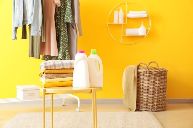 Rack con vestiti, bucato e detersivi sul tavolo in camera