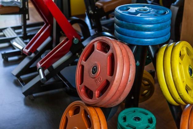 Rack con dischi bilancieri colorati in una moderna palestra