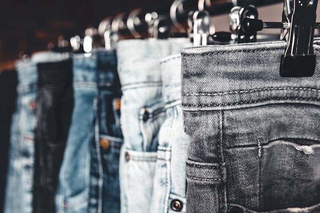 Rack con diversi jeans su sfondo grigio