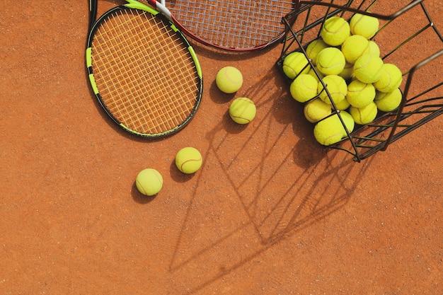 Racchette e cesto con palline da tennis su campo in terra battuta