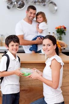 Madre radiosa che dà da mangiare a suo figlio a pranzo