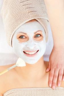 Radiosa giovane donna con crema bianca sul viso