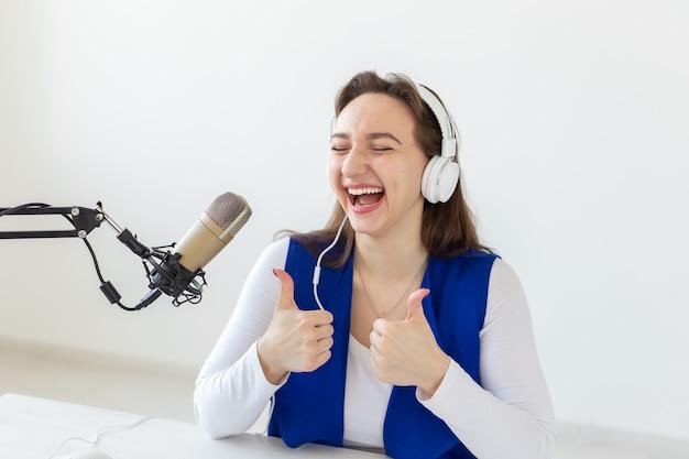 Radio, blog, concetto di trasmissione - giovane donna che lavora alla radio e mostra i pollici in su isolato su sfondo bianco.