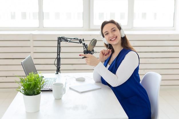 Radio, blog, concetto di trasmissione - giovane donna che lavora alla radio.