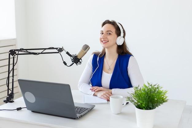 Radio, blog, concetto di podcasting - giovane donna che lavora come dj alla radio.