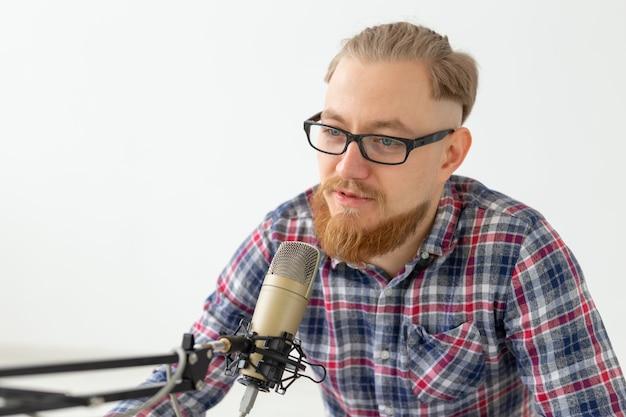 Radio, dj, blog e concetto di persone - primo piano dell'uomo seduto davanti al microfono, ospite alla radio