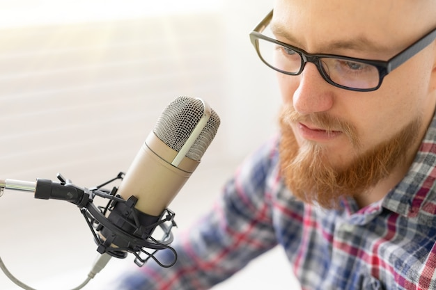 Radio, dj, blogging e concetto di persone - close-up di uomo seduto davanti al microfono