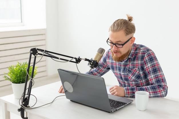 Radio, dj, blog e concetto di persone - uomo sorridente seduto davanti al microfono, ospite alla radio
