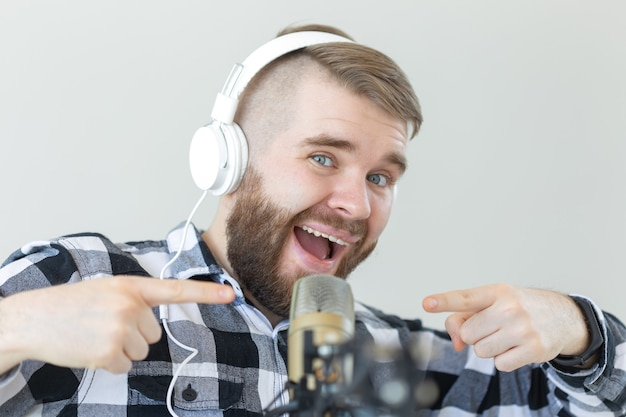 Concetto di radio e dj - l'uomo con il microfono e la grande cuffia sorride