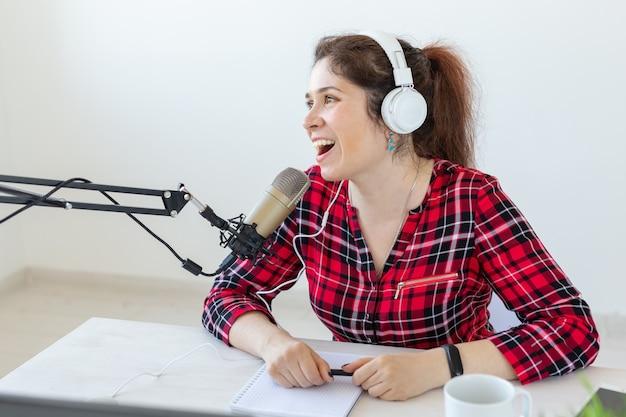 Conduttore radiofonico, blogging, concetto di trasmissione - giovane donna che lavora alla radio.