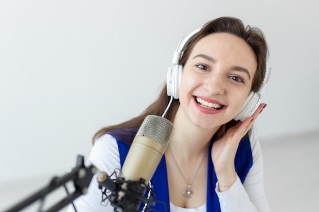 Concetto di host radiofonico - ritratto di presentatore radiofonico donna con le cuffie.