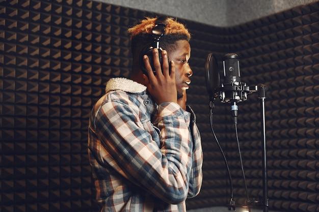 Conduttore radiofonico gesticolando durante la registrazione di podcast in studio radiofonico. l'uomo africano prova in uno studio di registrazione.