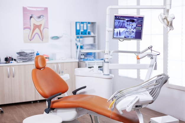 Radiografia della mascella del paziente sullo schermo in studio dentistico. apparecchiature per stomatologia in ospedale privato dentale senza nessuno al suo interno. diversi strumenti e strumenti dentali.