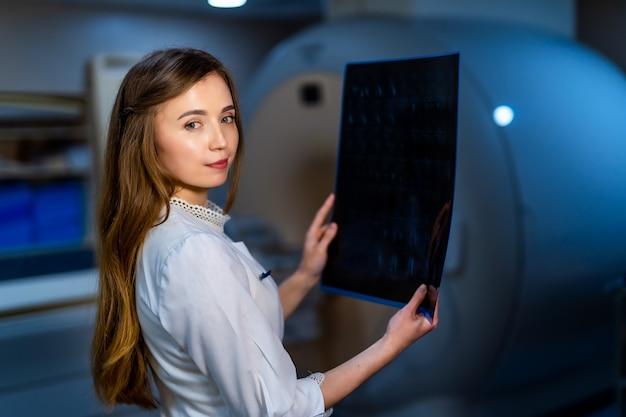 Medico femminile del radiologo con l'immagine dei raggi x in mani. macchina ct sullo sfondo.