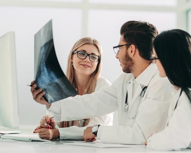 Il radiologo ei suoi colleghi discutono la radiografia del paziente