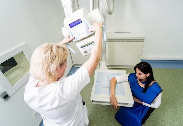 Radiologo e paziente in una sala radiologica. radiografia della mano umana. sistema di radiografia classica a soffitto.