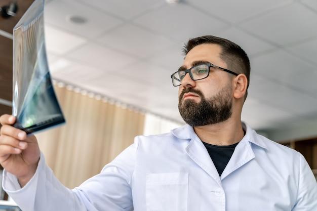 Radiologo con raggi x in mano. sfondo ufficio. uomo barbuto con gli occhiali.