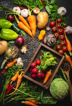 Mazzo fresco di ravanello e carota in una vecchia scatola di legno e verdure biologiche fresche di fattoria su fondo rustico di cemento nero. raccolto autunnale, cibo vegetariano o concetto di alimentazione sana e pulita, vista dall'alto