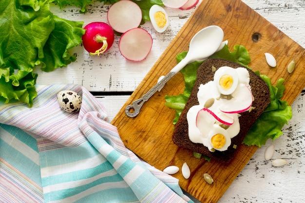 Ravanelli, lattuga e panna acida su un tavolo di legno, vista dall'alto.